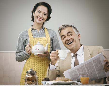 ama de casa: 1950 hermosa mujer servir el té para el desayuno a su marido sonriente Foto de archivo