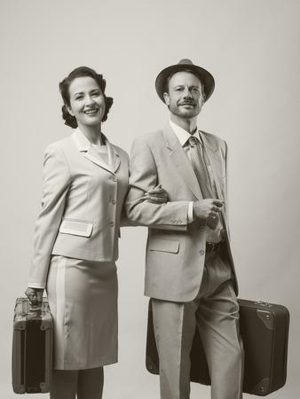 voyage vintage: Elégant couple d'amoureux laissant pour lune de miel avec des bagages, style des années 1950