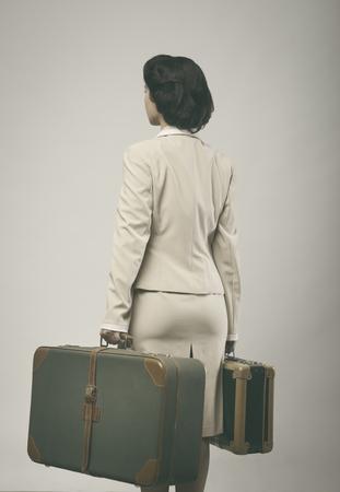 maleta: 1950 atractiva mujer de estilo sosteniendo maletas de visi�n trasera.