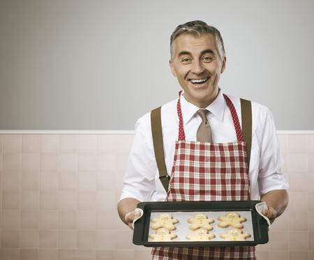 hombre cocinando: Hombre sonriente de la vendimia en el delantal de cocinar deliciosas galletas de pan de jengibre hombres en una bandeja para hornear