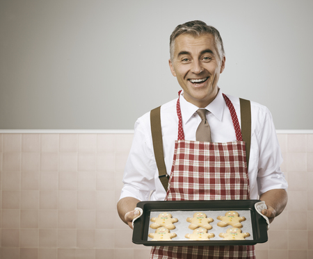Smiling vintage man in apron cooking delicious gingerbread men cookies on a baking tray