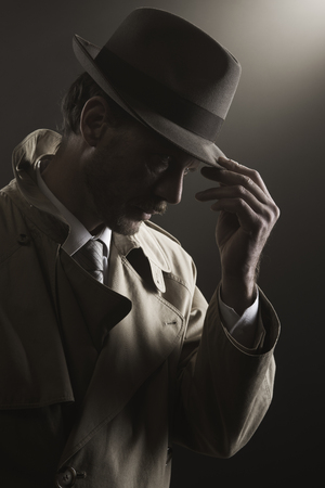 mobster: Detective adjusting his hat standing in the dark, film noir Stock Photo