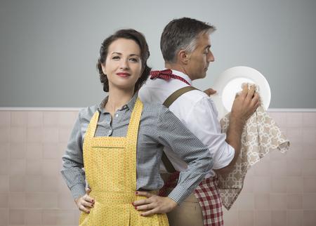 casalinga: Sorridente forte donna guarda il marito in cucina pulizia grembiule