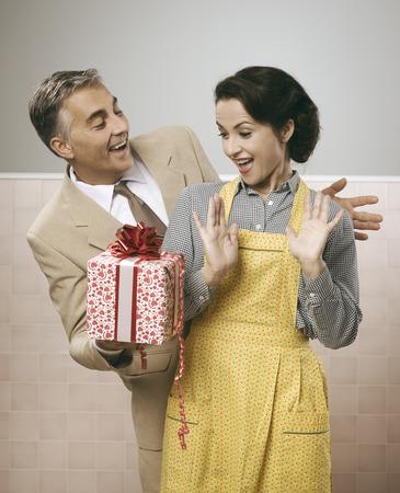 marido y mujer: Pareja romántica de la vendimia en la casa, le está dando a su esposa un hermoso regalo sorpresa Foto de archivo