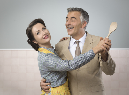 vintage kitchen: Smiling vintage couple dancing in the kitchen and holding a wooden spoon Stock Photo