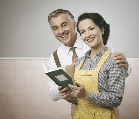 vintage kitchen: Vintage wife and husband reading a cookbook together at home