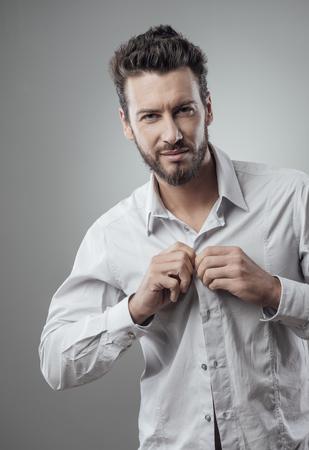 vistiendose: Hombre de moda atractiva que consigue listo para salir abrochándose la camisa Foto de archivo