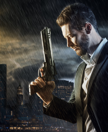 Brave handsome male agent under pouring rain holding a gun, city skyline and cloudy sky at sunset on background