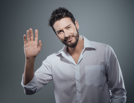 rolledup sleeves: Handsome man greeting somebody with hand raised