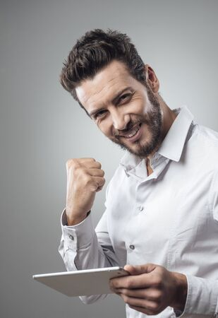 using tablet: Cheerful smiling man receiving good news on tablet with fist raised