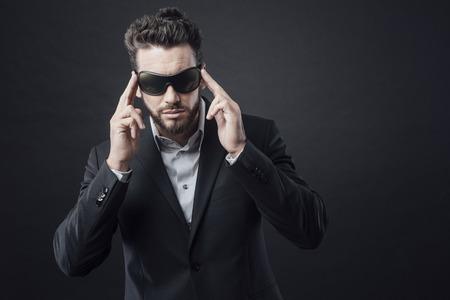 adjusting: Elegant attractive man posing and adjusting dark sunglasses