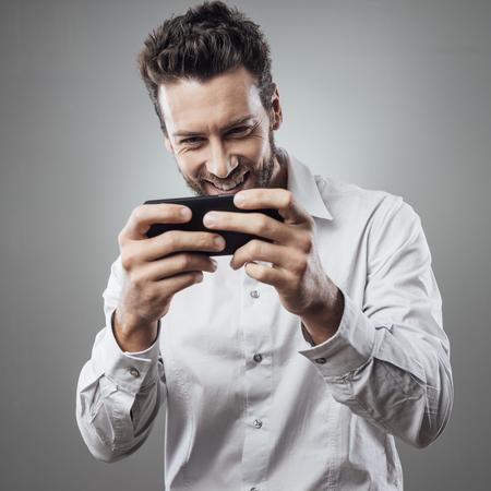 Gut aussehender junger Mann spielt mit seinem Smartphone