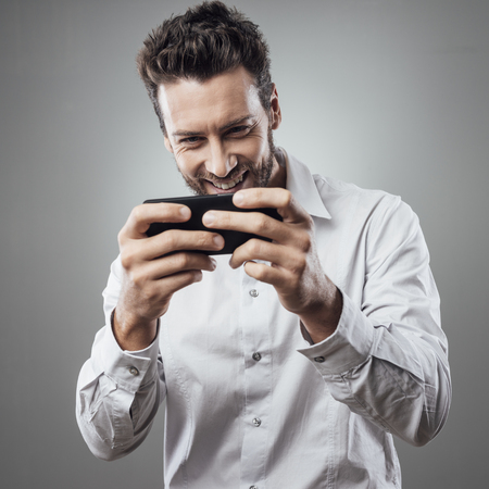 young adult men: Handsome young man playing with his smartphone