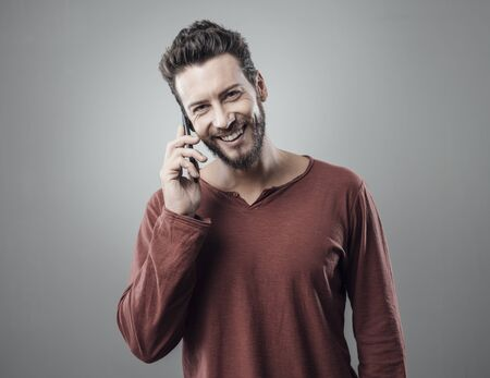 happy young man: Young smiling cheerful man having a phone call and looking at camera