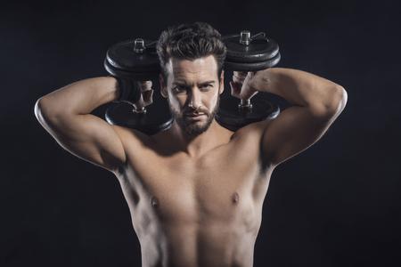 pesas: Hombre descamisado atractivo el ejercicio y el levantamiento de pesas en fondo oscuro