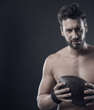 pigskin: Handsome confident football player holding ball and showing his athletic body