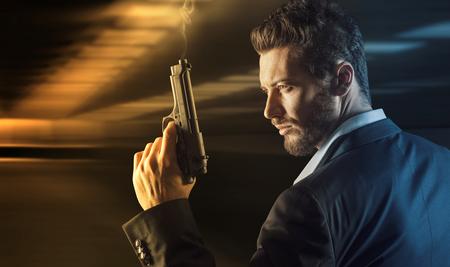 holding gun: Brave cool man holding a gun on dark background Stock Photo