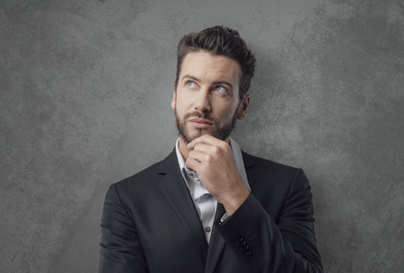 man's suit: Pensive young businessman thinking and planning strategies with hand on chin