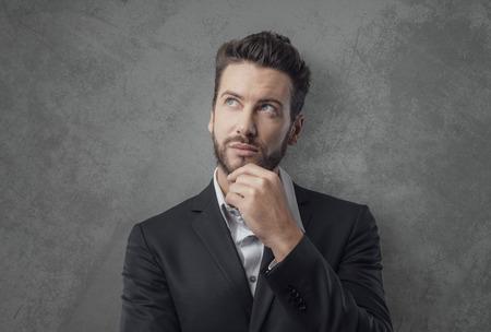 Snivý mladý podnikatel myšlení a plánování strategie s rukou na bradě