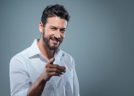 Modieuze knappe man die op camera met een sterke houding
