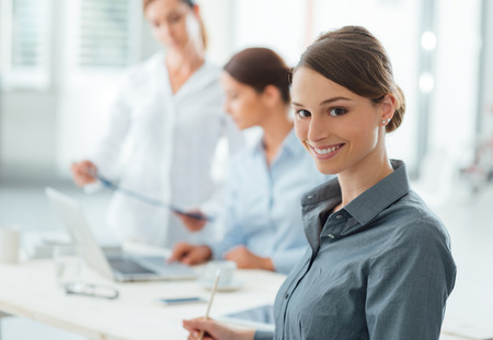 Smiling business woman posing and looking at camera and office workers talking on background