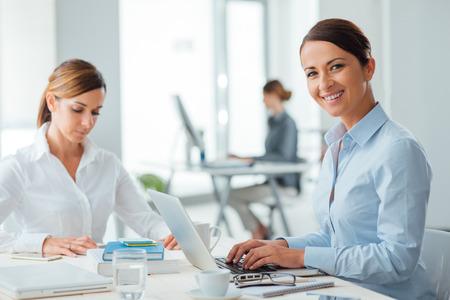 El éxito de las mujeres de negocios seguros y empresarios que trabajan en escritorio de oficina, uno está sonriendo a la cámara, interior de la oficina en el fondo