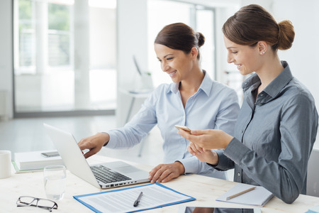Business women at office desk working together on a laptop, teamwork concept