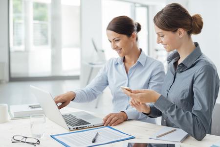 Mujeres de negocios en el escritorio de oficina trabajando juntos en un ordenador portátil, trabajo en equipo concepto