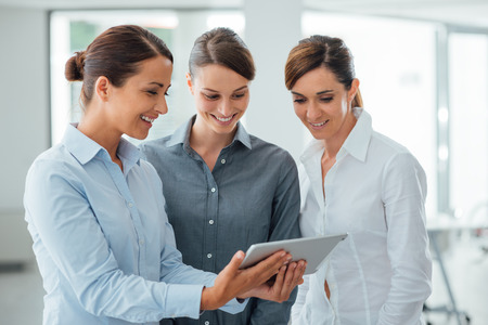woman in office: Professional smiling business women standing in the office and using a touch screen tablet, they are enjoying and watching the screen