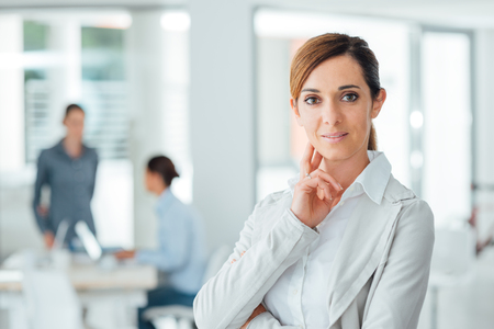 woman in office: Confident woman entrepreneur posing in her office and smiling at camera, success and women empowerment concept Stock Photo