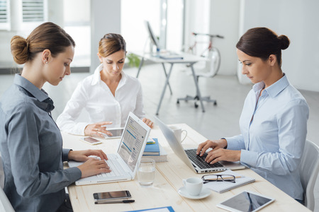 three people only: Confident professional women entrepreneurs working at office desk, they are typing on a laptop and using a tablet