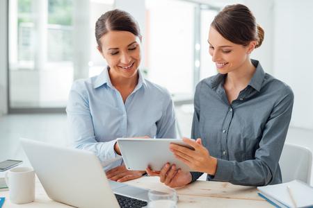 Mujeres de negocios profesionales que trabajan juntos en el mostrador de la oficina y el uso de una tableta de pantalla táctil