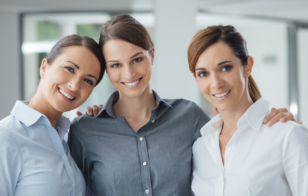 only women: Business women posing together in the office and smiling at camera, teamwork and women empowerment concept Stock Photo