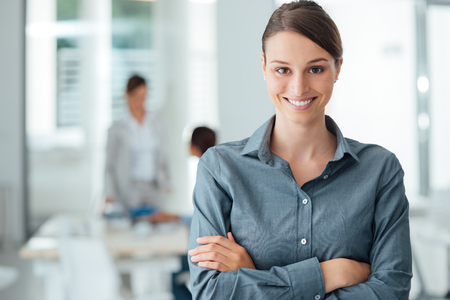 Smiling female office worker posing with arms crossed and looking at camera, office interior on background Stockfoto