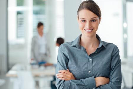 Lächelnde weibliche Büroangestellte posiert mit verschränkten Armen und Blick in die Kamera, Büro-Interieur auf Hintergrund Standard-Bild