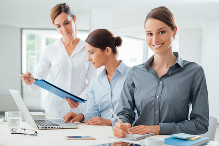 group work: Business women team working at office desk and pointing on a report, one is smiling at camera