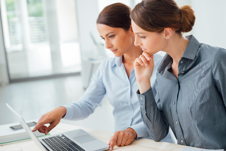 mujer trabajadora: Mujeres de negocios en el escritorio de oficina trabajando juntos en un ordenador port�til, trabajo en equipo concepto