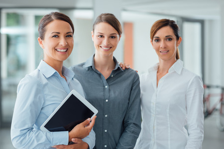 only women: Professional smiling business women standing in the office and smiling at camera, one is holding a digital tablet