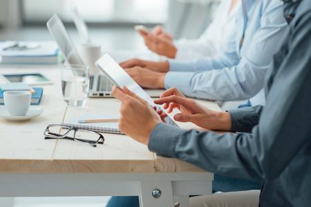 personas: Equipo de negocios que trabajan en escritorio de oficina utilizando una tableta, un ordenador portátil y un teléfono inteligente, las manos cerca, gente irreconocible