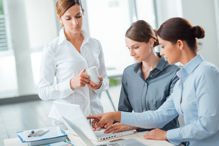 Successful women in business, they are working at office desk, pointing at computer screen and smiling Stock Photo