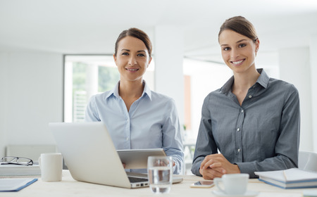 woman in office: Professional business women sitting at office desk and working together with a digital tablet, they are smiling at camera