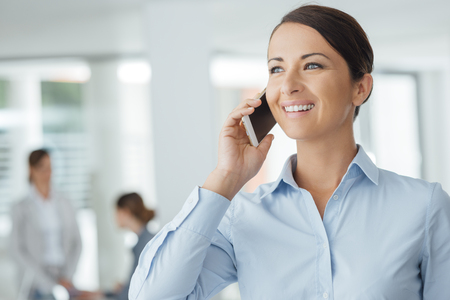 executive woman: Smiling confident business woman holding a smart phone and calling, office interior and business people on background, selective focus Stock Photo