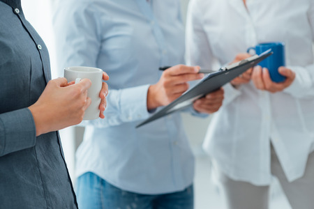 only three people: Business team discussing during a coffee break, holding mugs and writing on a clipboard, hands close up, unrecognizable people