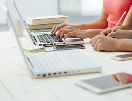 Las adolescentes que estudian en el escritorio y haciendo tareas, uno está utilizando un ordenador portátil y el otro está escribiendo en un cuaderno, concepto de la educación, la gente irreconocible Foto de archivo - 44839311