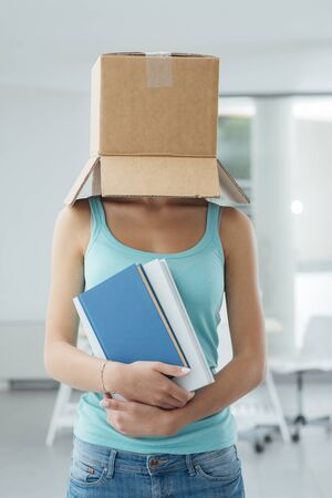 boxed: Young student standing with a box on her head and holding books, loneliness and conformity concept
