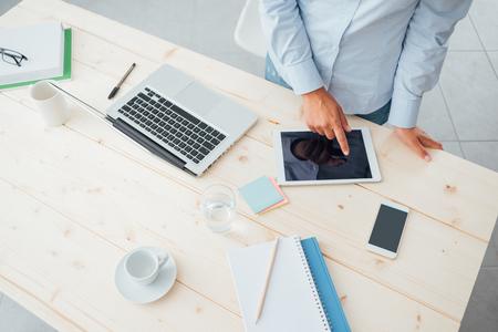Nicht erkennbare Geschäftsfrau, die am Schreibtisch und mit einem Touch-Screen-Tablet auf einem hölzernen Oberfläche