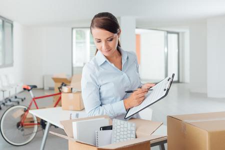 Sourire d'affaires écrit une liste de contrôle de réinstallation pour son bureau sur un presse-papiers et la recherche dans une boîte en carton ouverte Banque d'images