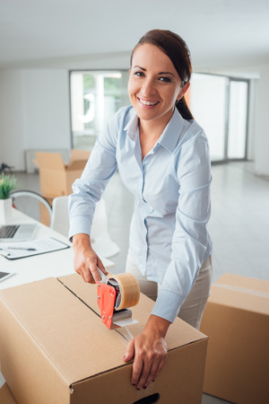 moving office: Young business woman taping up a cardboard box in the office, relocation and new business concept