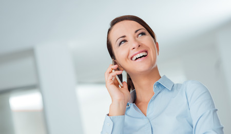 confident woman: Smiling confident business woman having a phone call with her mobile phone, office interior on background Stock Photo