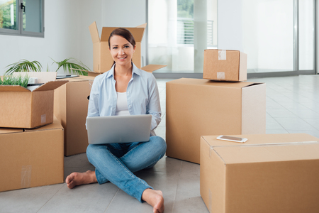 moving in: Beautiful woman moving in her new house and unpacking, she is sitting on the floor surrounded by boxes, using a laptop and smiling at camera